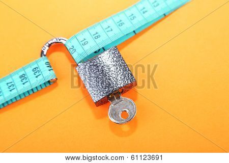 Conceptual photo of unlocking  secret of weight loss. On color background