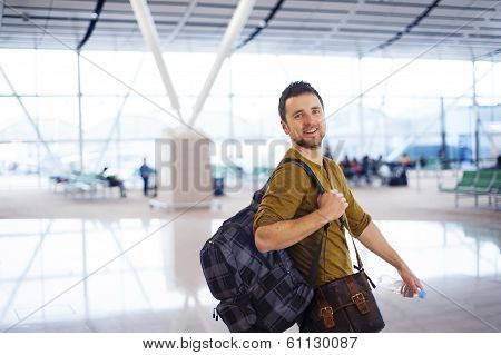 Happy man at the airport is going for holiday