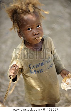 KOLMINY, HAITI - FEBRUARY 12, 2014.  A malnourished preschooler eating peanut butter bread received from a mission.
