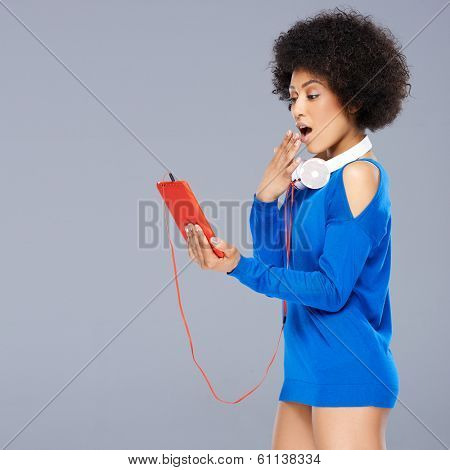Shocked woman looking at her music storage device with her hand raised to her open mouth as she views something on the screen with the earphones dangling round her neck