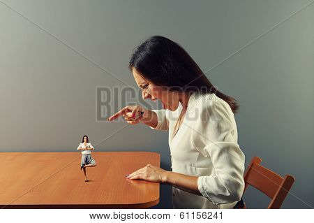 angry young woman screaming at small calm woman on the table