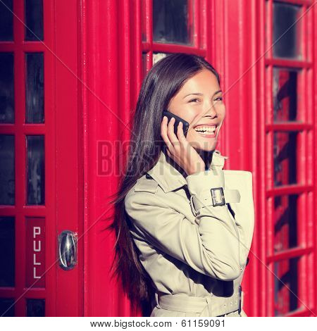 London woman on smart phone by red phone booth. Young casual female business woman having conversation on mobile smart phone in London, England, United Kingdom. Multiracial Asian Caucasian model