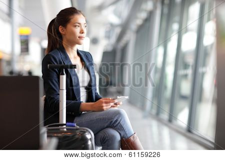 Passenger traveler woman in airport waiting for air travel using tablet smart phone. Young business woman smiling sitting with travel suitcase trolley, in waiting hall of departure lounge in airport.