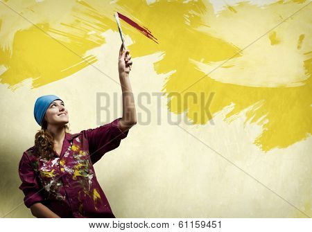 Young woman painter in bandana with paintbrush in hand