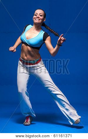 Young dancer in movement on blue background