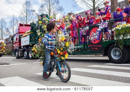 Lisse, Netherlands - April 20, 2013: Boy on bicycle on flower parade. The annual Flower Parade in Holland between Noordwijk and Haarlem is a 42 km feast of beautiful colors and enticing aromas.