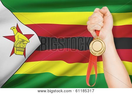 Medal In Hand With Flag On Background - Republic Of Zimbabwe