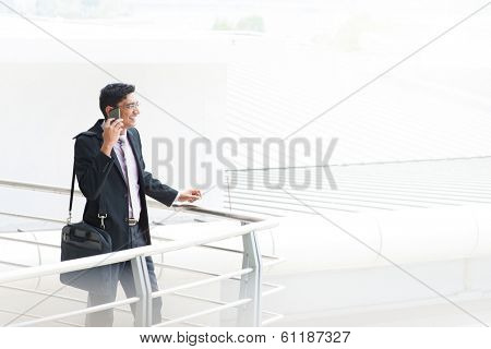 Candid young Asian Indian businessman on the phone at outdoor building. India male business man, real modern office building as background.