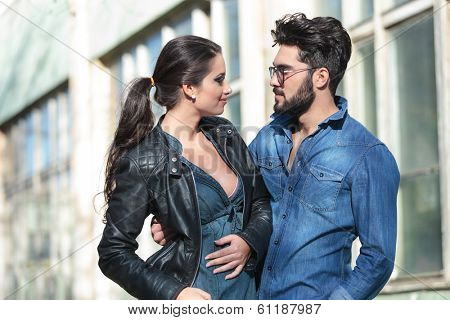 young casual couple looking at each other and smiling while he is embracing her