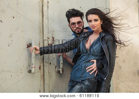 beautiful young casual couple embracing outdoor, in the wind, while looking into the camera and holding on to a rusty old door