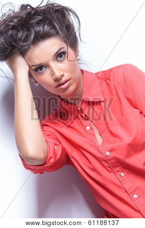 diagonal view of a casual young woman looking into the camera and holding her hand in her hair. on white studio backgroud