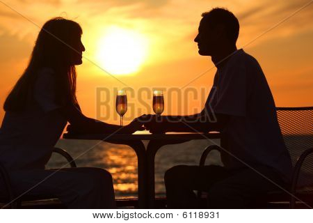 Couple's Silhouettes On Sunset Sit At Table With Two Glasses
