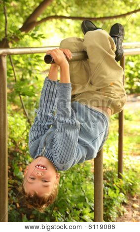 Boy Hangs On Bars Headfirst