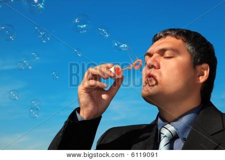 Businessman Blows Soap Bubbles Against Sky