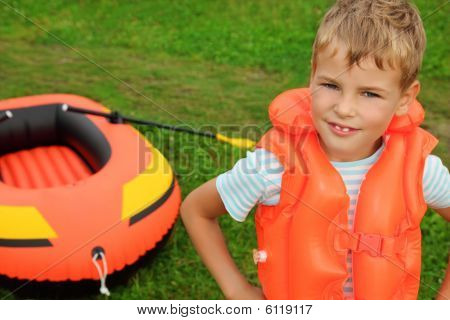 Boy And Inflatable Boat On Lawn