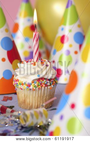 Birthday cupcake with party hats and lit candle