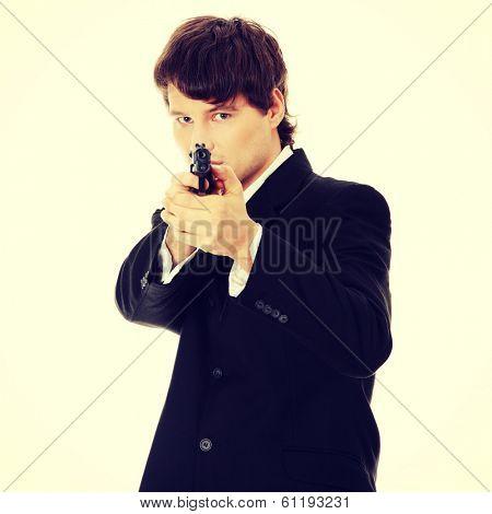 Businessman aiming with handgun