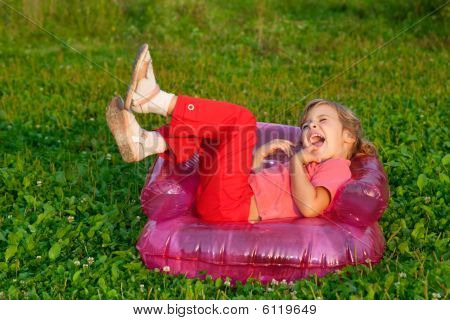 Young Girl Playing Tricks In Inflatable Armchair Outdoors