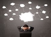 image of wall cloud  - Young businessman sitting in office chair in front of a wall with cloud technology concept above his head - JPG