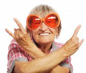 foto of retirement age  - Senior woman wearing big sunglasses doing funky action isolated on white background - JPG