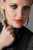 picture of blazer  - Portrait of beautiful blond woman with studio pulled back wearing diamante statement earrings and blazer with beads on studio background - JPG