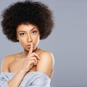 image of silence  - Beautiful African American woman with a large afro hairdo making a hushing gesture holding her finger to her lips as she requests silence - JPG