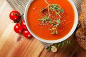 stock photo of dark side  - Fresh gourmet tomato soup with fresh herbs and pepper - JPG