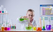 foto of naturalist  - Image of funny young chemist pouring reagent into flask - JPG