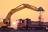 picture of risen  - heavy wheel excavator machine working at sunset - JPG