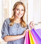 Closeup portrait of happy customer with colorful paper bag in great mall, attractive girl enjoying s