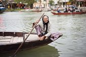 picture of toothless smile  - Old smiling elderly woman sailing canoe on the river in Vietnam - JPG