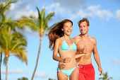 Couple having fun on beach vacation travel laughing happy running together playful and joyful. Woman