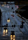 stock photo of icy road  - Cars with headlights shinning on stormy wet road driving in rain - JPG