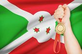 image of burundi  - Sportsman holding gold medal with flag on background  - JPG