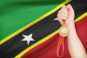 Medal In Hand With Flag On Background - Federation Of Saint Christopher And Nevis
