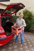 image of crate  - a young woman lifts a crate of bottles from their car - JPG