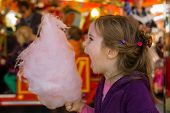 a little girl on a kirtag with cotton candy. fun and joy of fair
