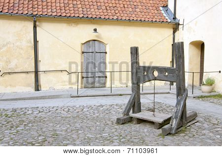 An old wooden lockup, pillory on a yard.