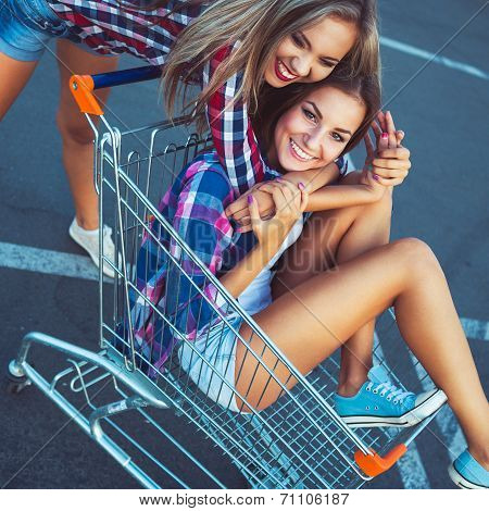 Two Happy Beautiful Girls In Shopping Cart Outdoors, Lifestyle Concept