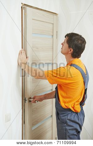 Male handyman carpenter at interior wood door installation