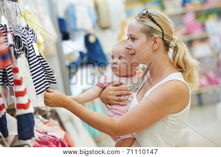 woman choosing children apparel with little baby child on hands in clothing shop supermarket