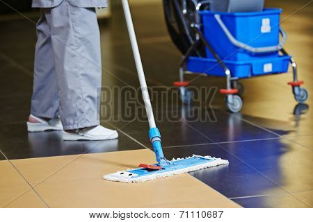 cleaner with mop and uniform cleaning hall floor of public business building