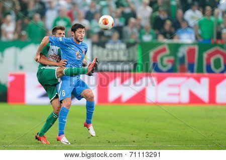 VIENNA, AUSTRIA - AUGUST 22 Christopher Trimmel (#28 Rapid) and Giorig Guruli (#6 Dila Gori) fight for the ball at a UEFA Europa League game on August 22, 2013 in Vienna, Austria.