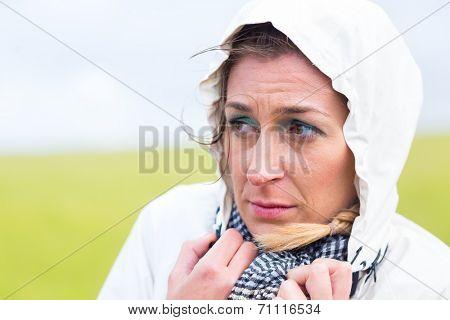 Woman freezing in rain shower at German north sea coast