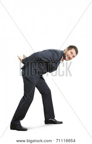 smiley young businessman stooping down and walking. full length photo over white background