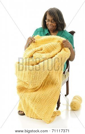 A senior woman finishing the gold afghan she's been making.  On a white background.