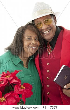 Portrait of a happy senior couple dressed in red, green and white.  She carries a pot of poinsettias.  He carries his Bible.  On a white background.