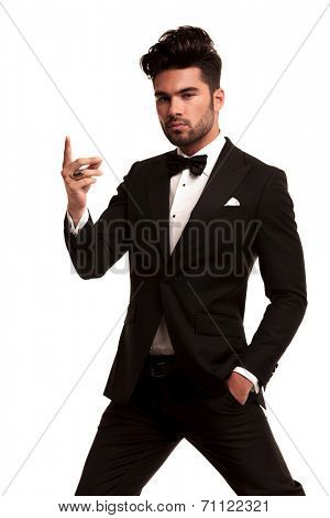 imposing fashion man in tuxedo snapping his fingers on white background