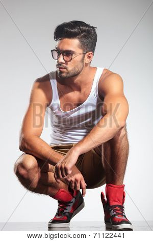 crouched fit casual man looking to his side on grey studio background
