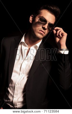 man puts on his sunglasses and looks to his side on black background